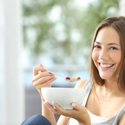 Woman dieting and eating cornflakes sitting on a couch at home